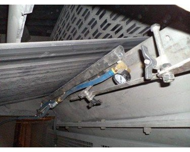 "A Model 110048PKI 48"" (1219mm) Super Air Knife with Plumbing Kit installed uses Universal Air Knife Mounting Systems to maintain proper position for removing dust on a conveyor belt and eliminate carryover accumulation."