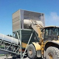 Dry fog application in surge and front end loader hoppers
